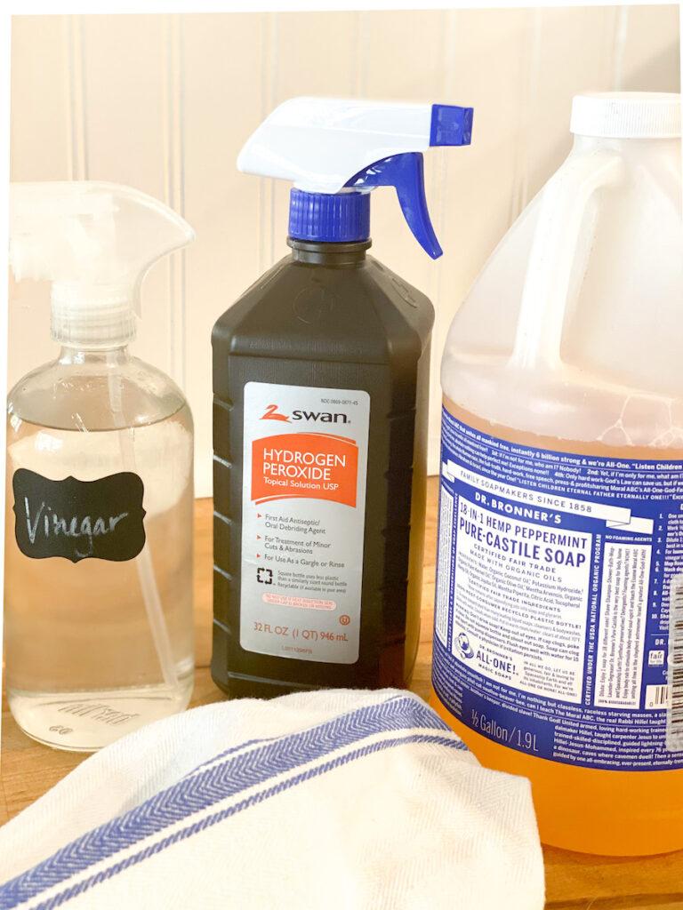 Vinegar in glass bottle, hydrogen peroxide, Castile soap, blue and white rag
